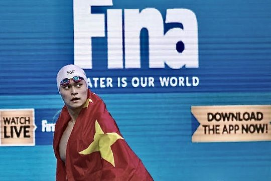 Sun Yang walks past a FINA banner at the 2017 World Championships - by Patrick B. Kraemer